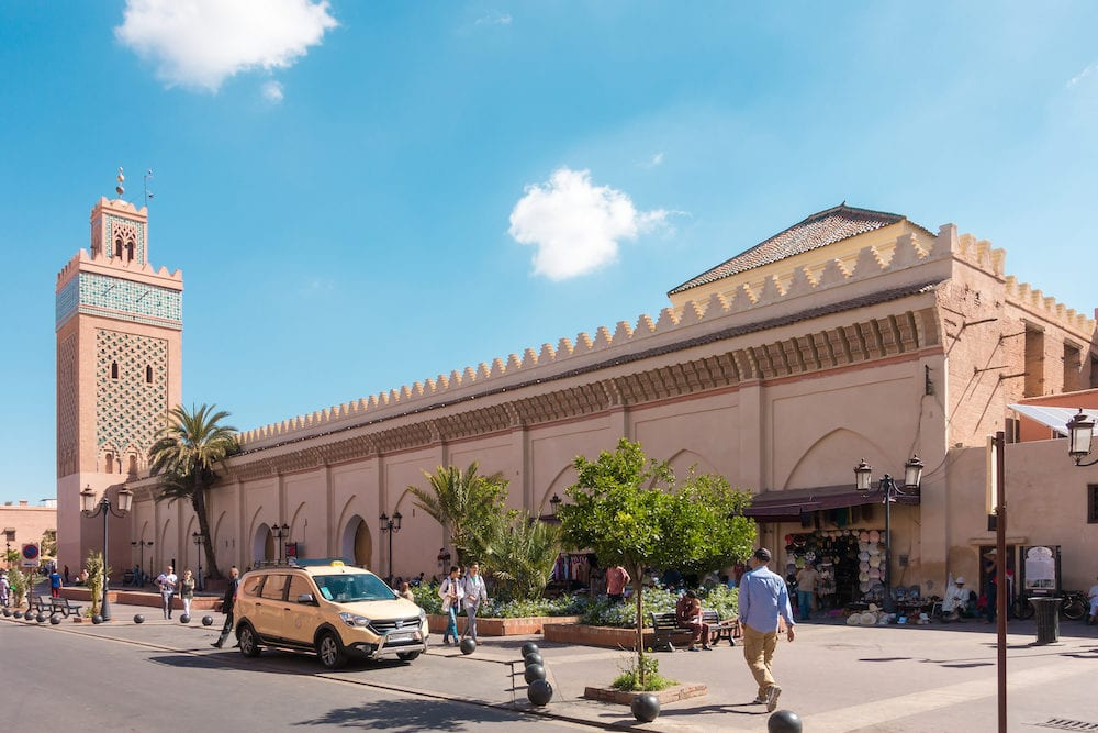 Marrakech Morocco. Shop owners and a taxi are waiting for customers while people are walking past the Moulay El Yazid Mosque in Marrakech Morocco on a sunny morning