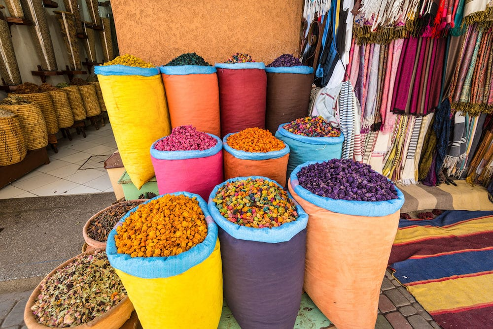 Marrakesh, Morocco - Piles of vibrant, colourful herbs and potpourri in bags at a market stall in a souk in Marrakech, Morocco.