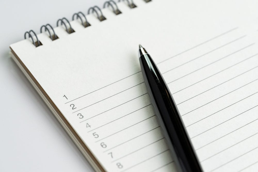 Personal to do lists or new year's resolution concept by closed up of list of numbers on white clean notepad with pen on it.