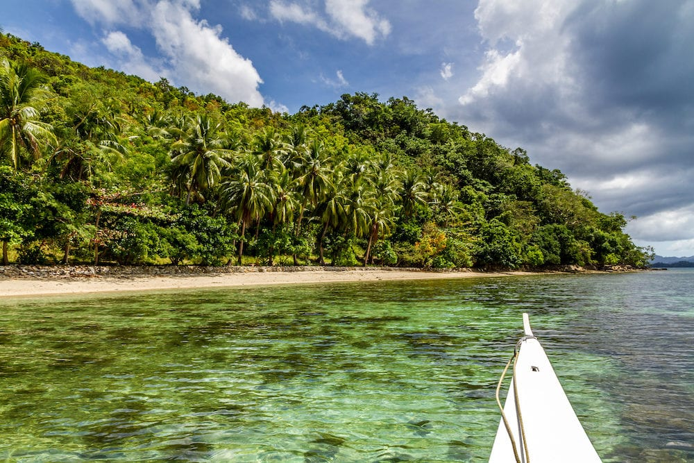 Empty Port Barton Beach with Boat and Palm Trees Palawan Philippines