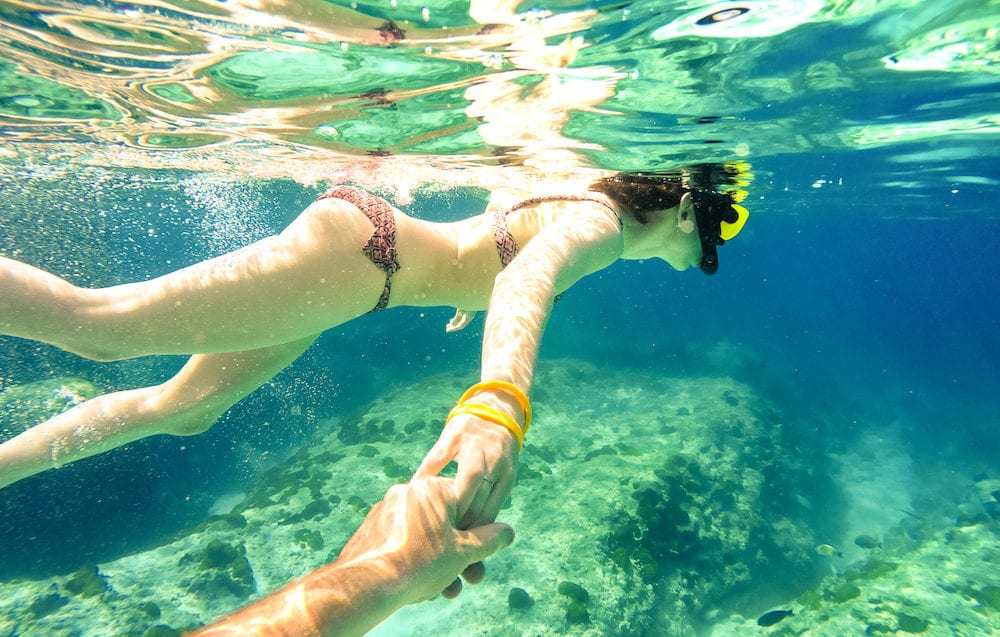 Snorkel couple swimming together in tropical sea with follow me composition - Snorkeling tour in exotic diving scenarios - Fun travel concept with active girl underwater - Soft focus due water density