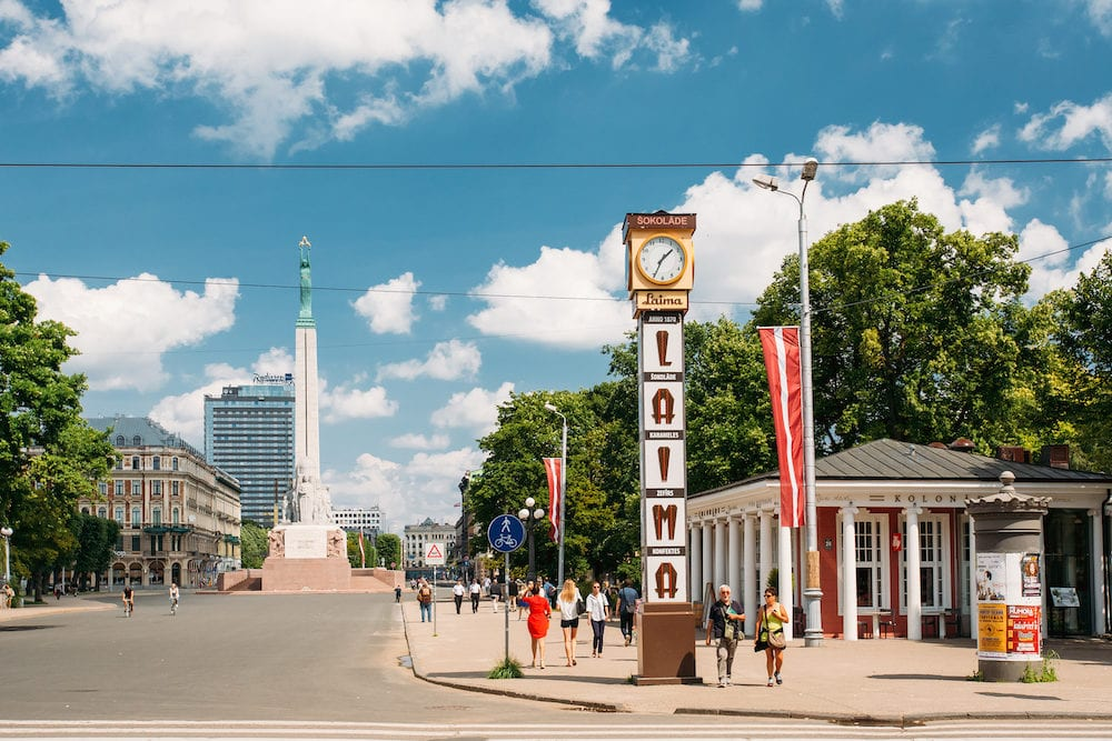 Riga, Latvia - People Walking Near Local Landmark Is Laima Clock In Sunny Summer Day. Now It Is One Of Landmarks And An Advert For The Laima Chocolate Company