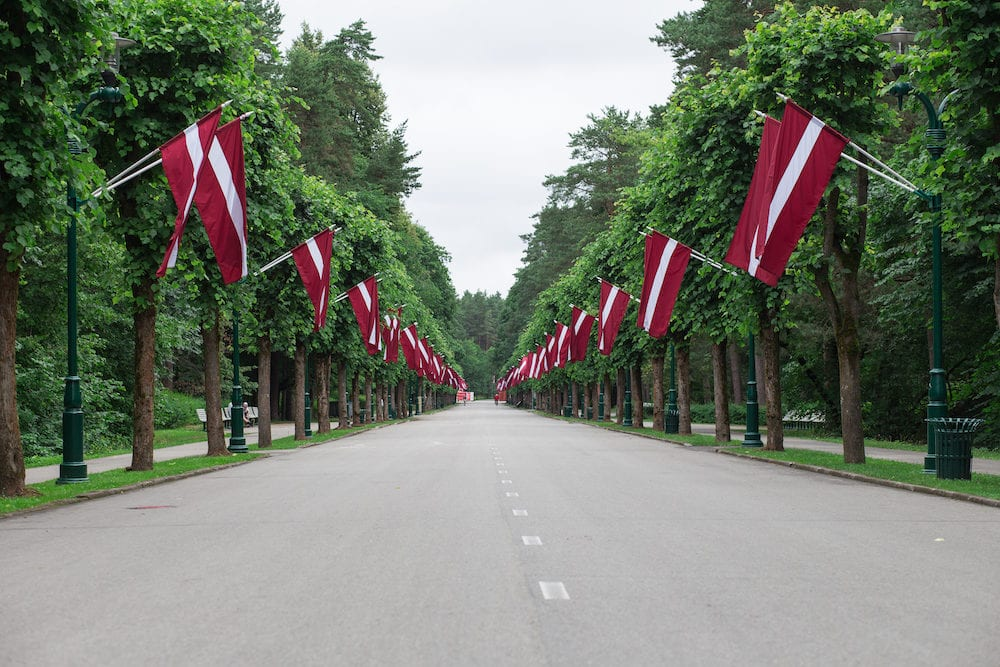 City Riga, Latvia. Park with Latvian flags and way. Place Mezaparks. Travel photo .