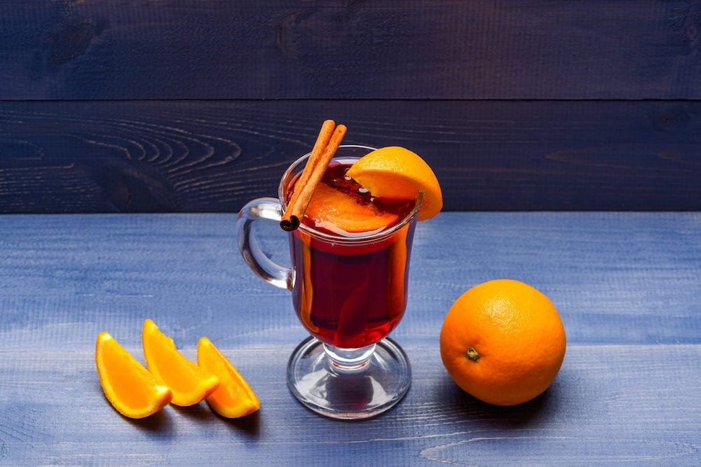 Drink or beverage with orange and cinnamon. Mulled wine with orange juice. Drink and cocktail concept. Glass with mulled wine near juicy orange fruit on dark blue background.