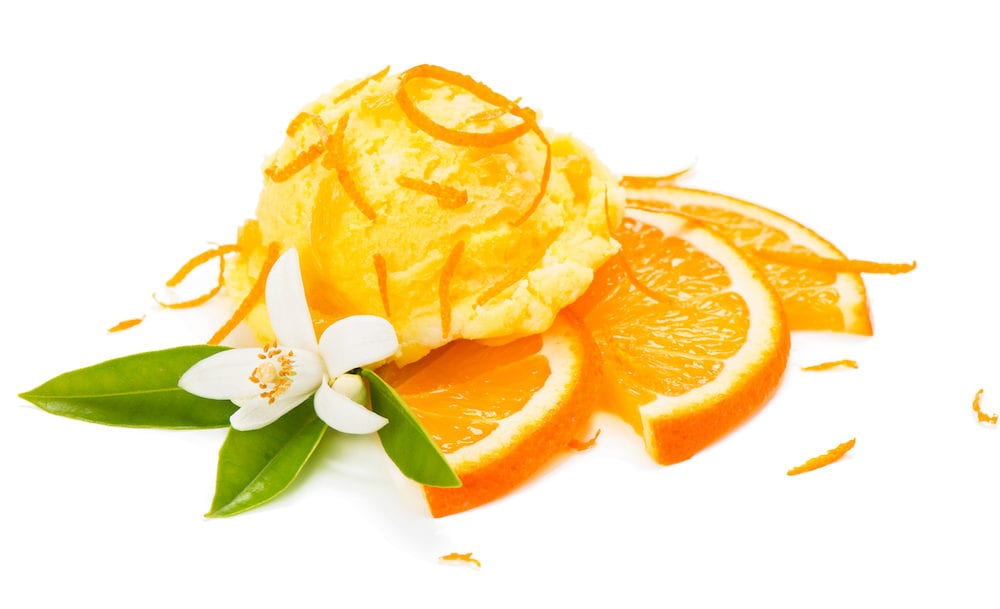 Orange ice cream decorated with zest and blossom isolated on white background