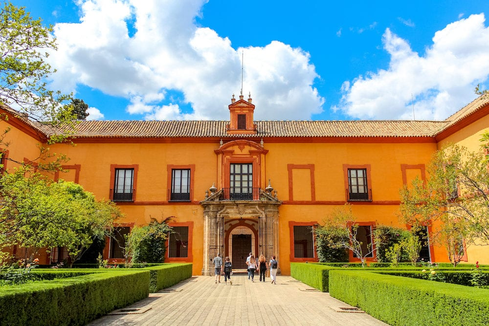 Seville, Spain -Courtyard of Royal Alcazar of Seville (Real Alcazar de Sevilla) Some tourists entering the building.