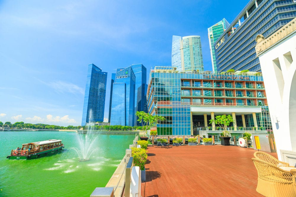 Singapore - : beautiful view of Fullerton Bay Hotel at five-star luxury, Singapore skyscrapers Business District and tourist boats along Marina Bay Promenade in a sunny day, blue sky.