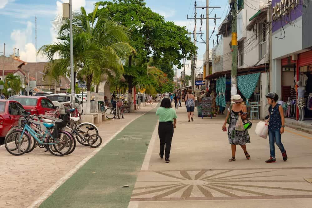 Tulum, Mexico - People walking on the sidewalk on Avenida Tulum.