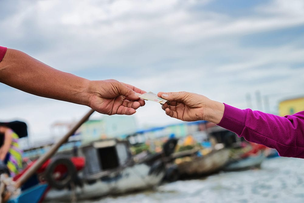 The moment of purchase and exchange of money for the goods at the Floating market at the delta Mekong in Can Tho, Vietnam