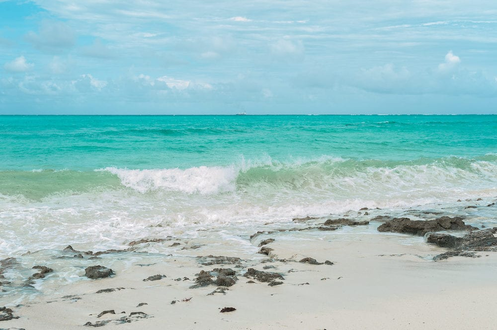 Turquoise waves of the Indian ocean run on the white beach of the island of Zanzibar.