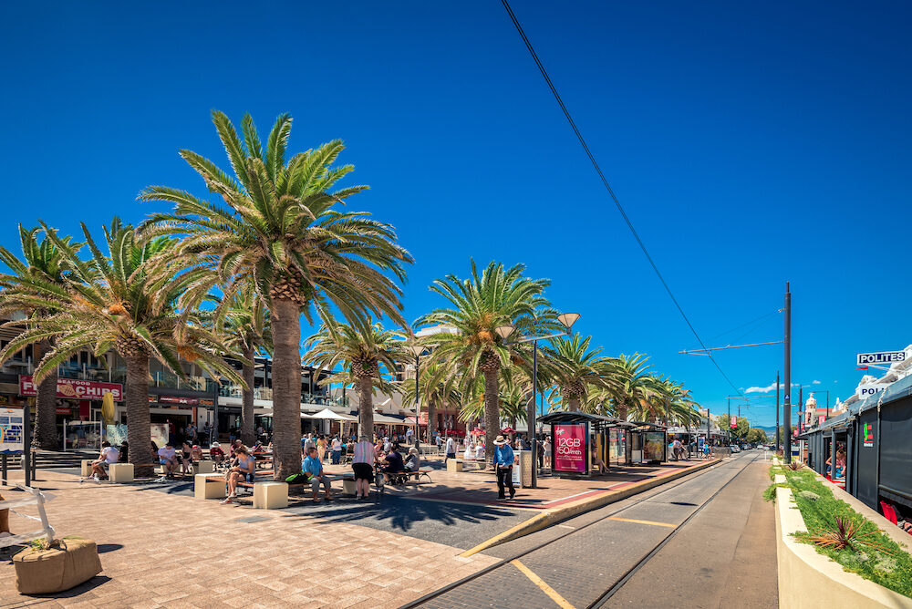 Glenelg, South Australia - : People relaxing at Moseley Square in Glenelg on a bright summer day viewed towards tram line