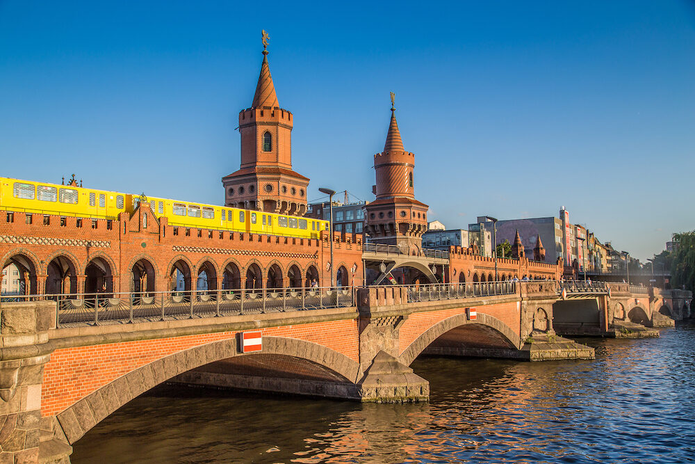 Classic panoramic view of famous Oberbaum Bridge with historic Berliner U-Bahn crossing the Spree river on a beautiful sunny day with blue sky in summer Berlin Germany
