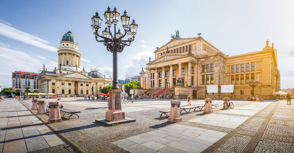 Panoramic view of famous Gendarmenmarkt square with Berlin Concert Hall and German Cathedral in golden evening light at sunset with blue sky and clouds in summer, Berlin Mitte district, Germany