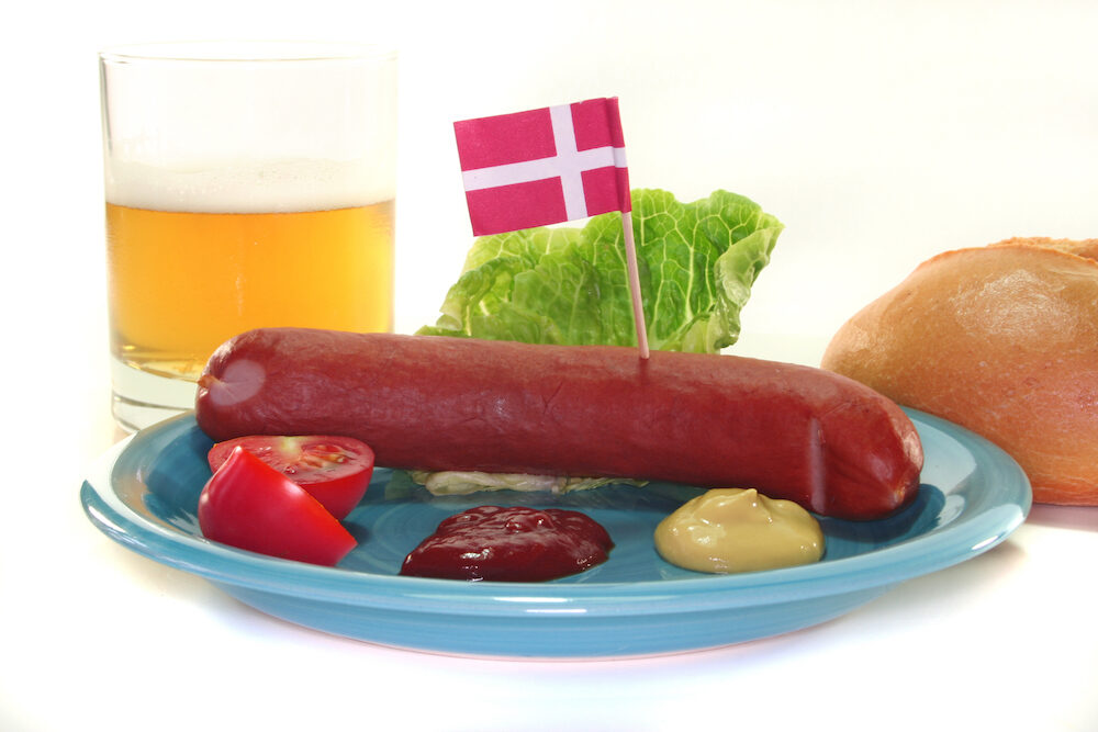Danish sausage with ketchup mustard salad bread and beer