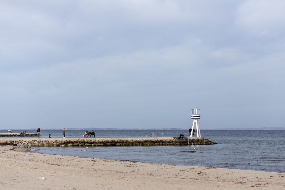 Klampenborg, Denmark - : People at one of the iconic lifeguard towers at Bellevue Beach just North of Copenhagen