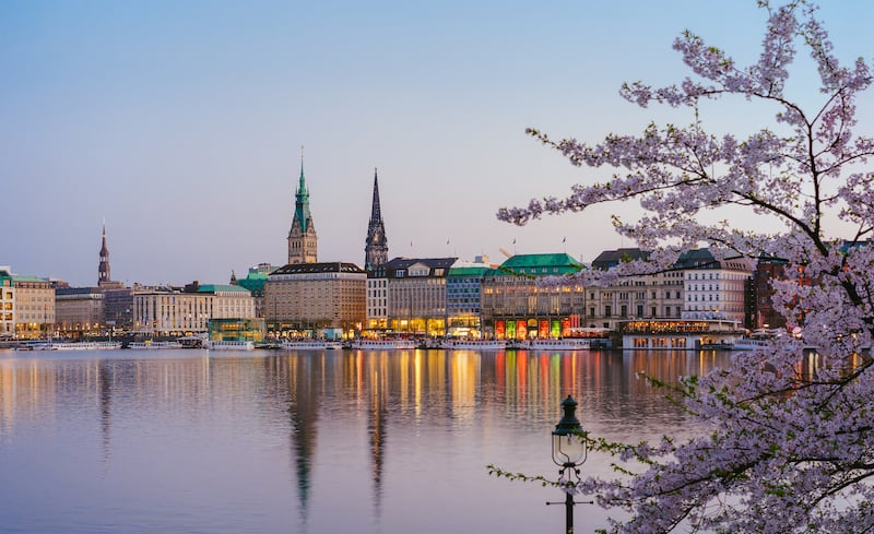 Beautiful panoramic view of Alster river and Hamburg town hall - Rathaus at spring earning evening during golden hour. Panoramic Banner shot.