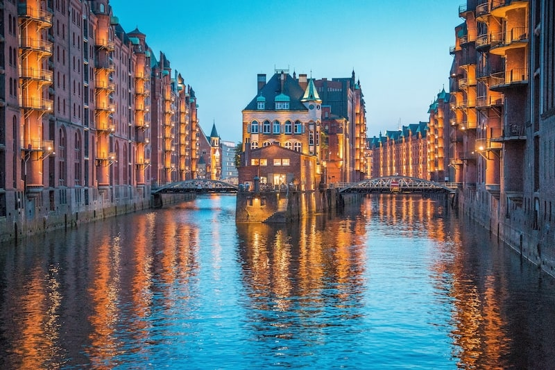 Classic view of famous Speicherstadt warehouse district, a UNESCO World Heritage Site since 2015, illuminated in beautiful post sunset twilight at dusk, Hamburg, Germany