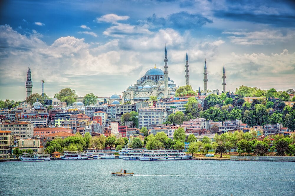 ISTANBUL TURKEY - View of the Suleymaniye Mosque and fishing boats in Eminonu Istanbul Turkey