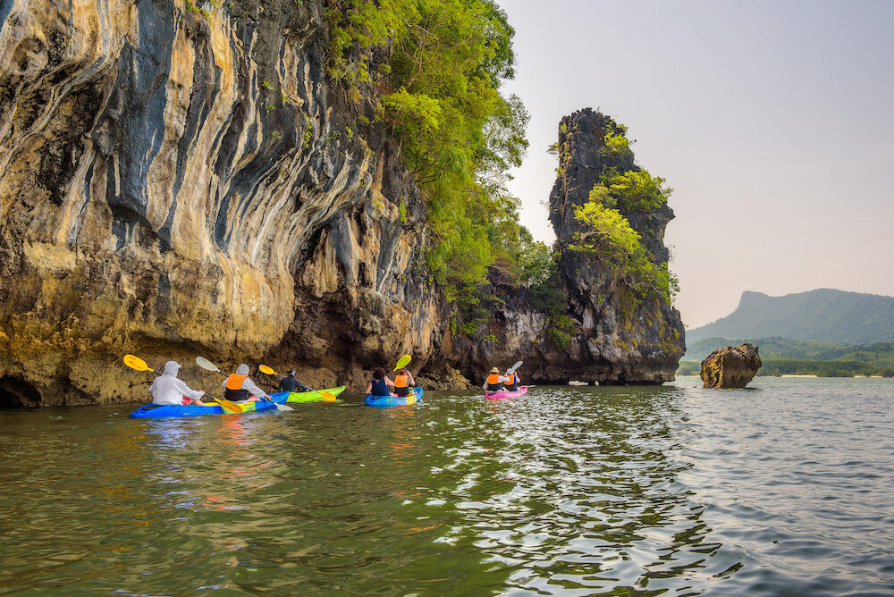 Phang Nga Bay, Thailand - Group of tourists kayaking into mangrove jungle of Krabi in Thailand