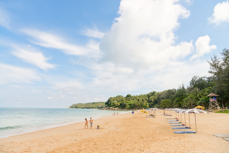 PHUKET THAILAND - Popular Surin beach with sunshade parasols on clear sand with calm blue sea