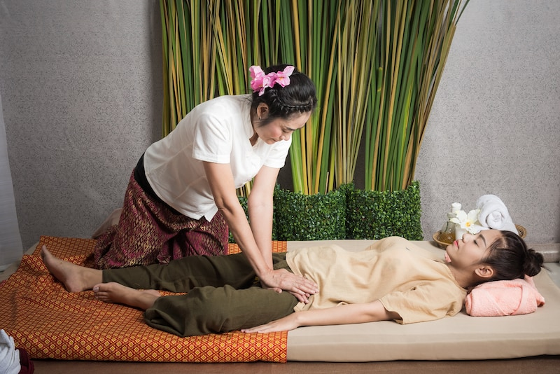 Thai Masseuse doing massage for lifestyle woman in spa salon. Asian beautiful woman getting Thai herbal massage compress massage in spa.She is very relaxed. Healthy Concept.