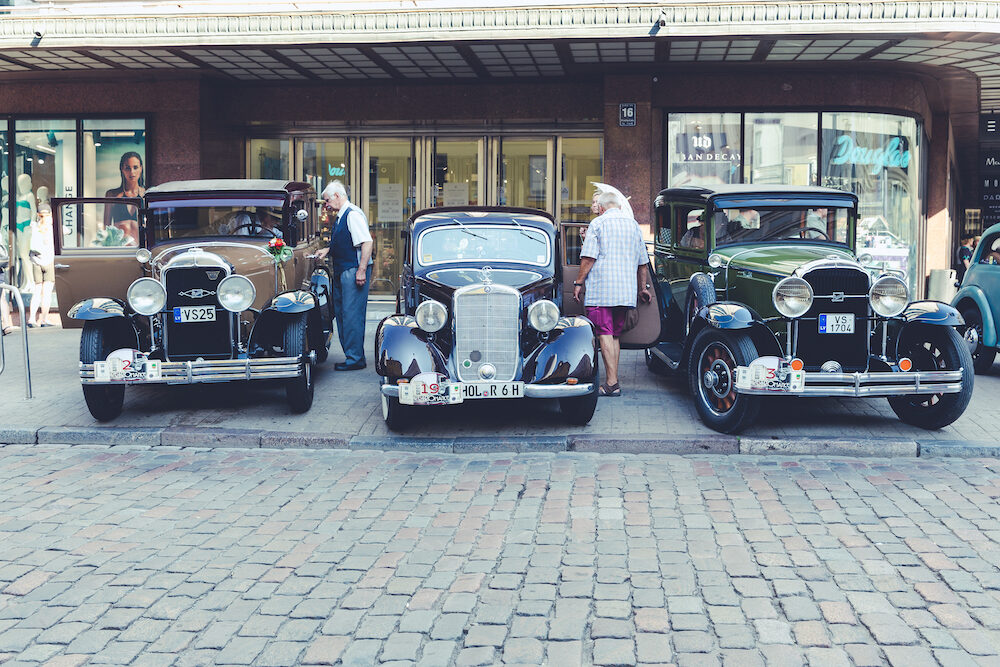City Riga, Latvia. Oldtimer car festival at capital Riga. Urban city view, peoples, cars and buildings.