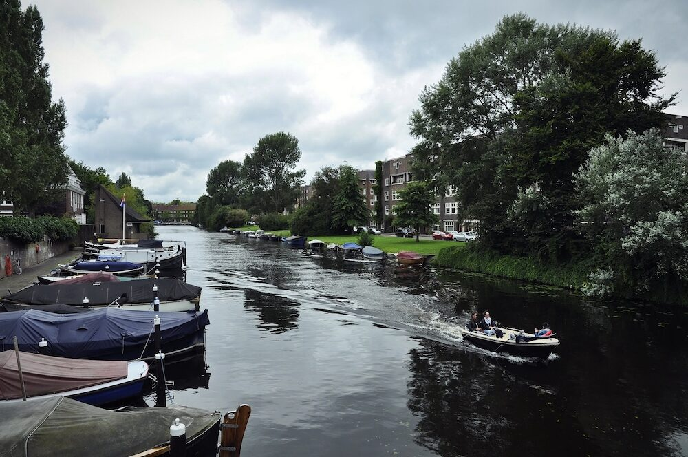 Apollobuurt, Amsterdam, the Netherlands - The waterscape of the North Amstel Canal (Noorder Amstelkanaal) from the Lyceum Bridge (Lyceumbrug) under cloudy sky, with a private boat with three passengers cruising across the horizon.