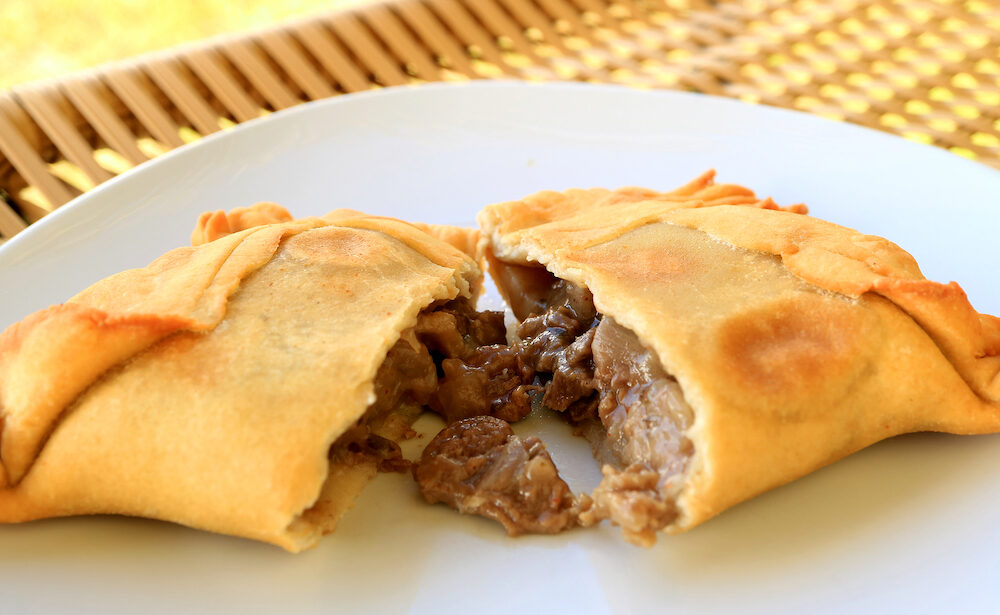 Beef filled Empanada or Empanada de Pino, delicious Chilean baked pasty served on white plate