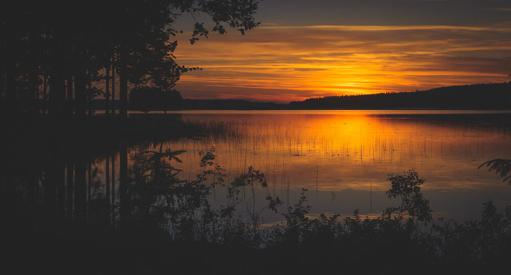 A calm sunset on a lake on midsummer midnight in Finland