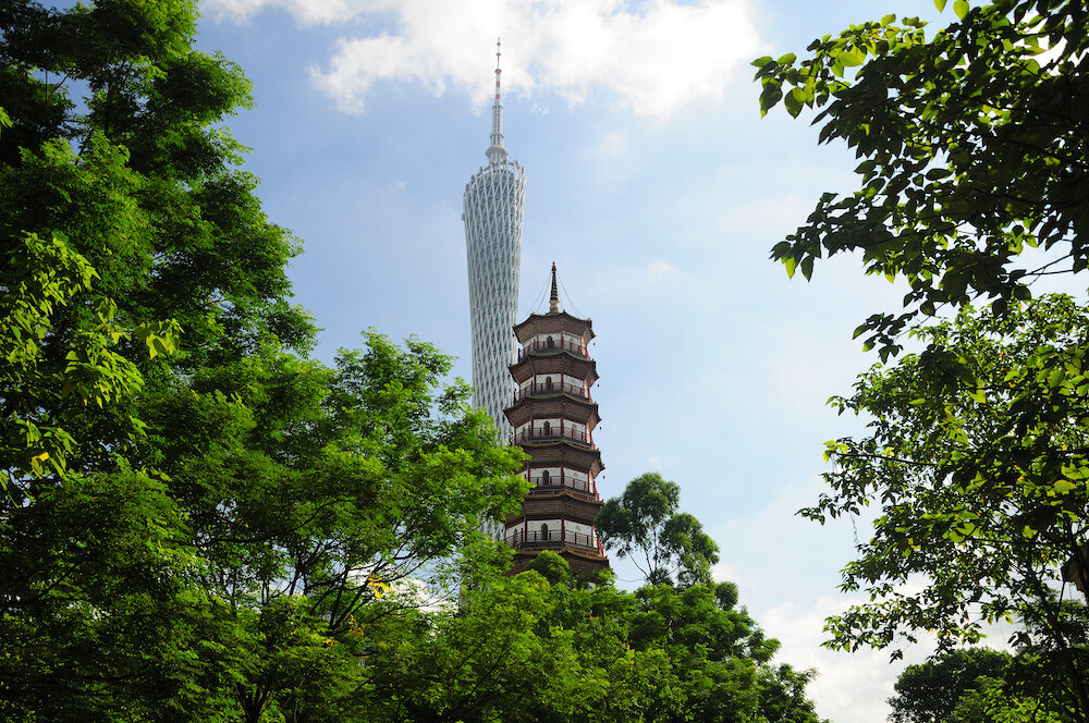 The Canton tower and Chigang Pagoda rising about a small park in the Haizhu district of Guangzhou china on a sunny blue sky day in Guangdong province.