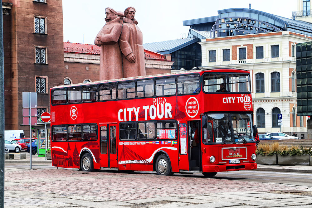 Riga, Latvia - Touristic red double-decker hop-on hop-off City Sightseeing tour bus on the street of Riga city
