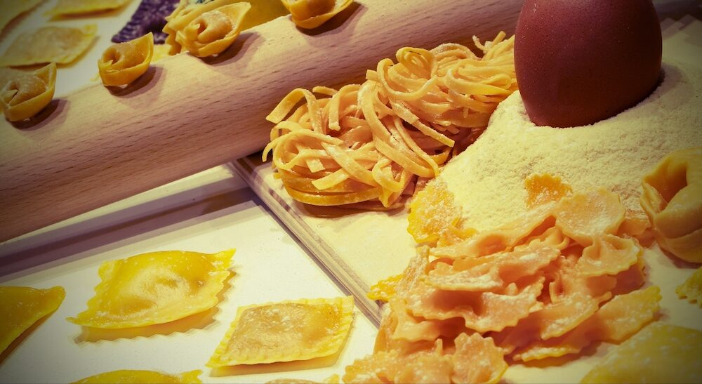 Organic ingredients to make homemade fresh pasta with flour and eggs and vintage effect