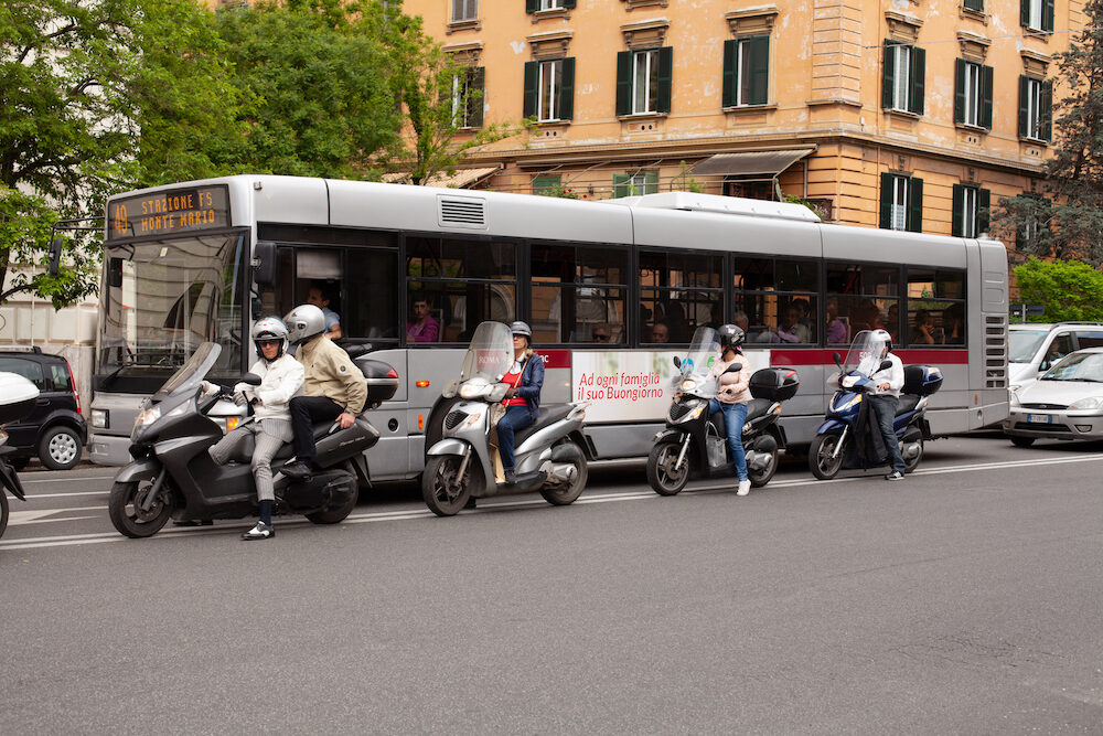Vatican City, Italy, People stopped in traffic on scooters beside a public bus on the streets of Rome, Italy