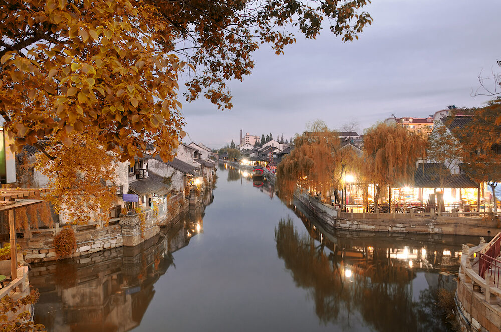 The buildings and water canals of Fengjing Town in Shanghai China at dusk with autumn colors.