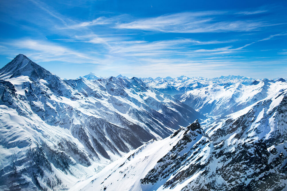 Aerial view of the Alps mountains in Switzerland. View from helicopter in Swiss Alps. Mountain tops in snow. Breathtaking view of Jungfraujoch and the UNESCO World Heritage – the Aletsch Glacier