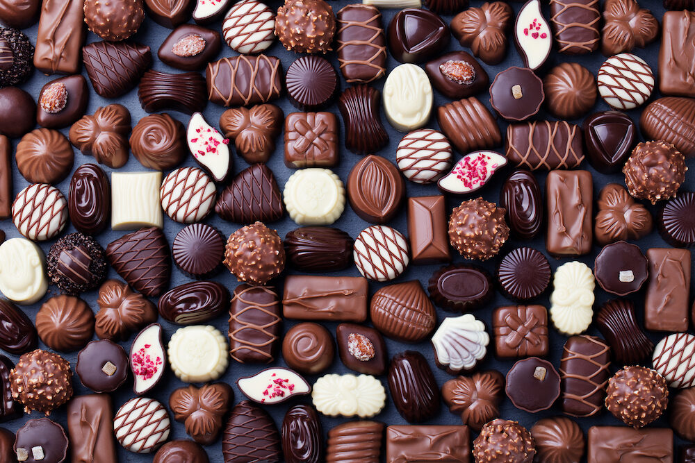 Assortment of fine chocolate candies white dark and milk chocolate Sweets background Copy space Top view