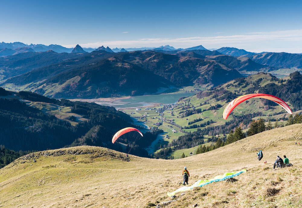 Einsiedeln, SZ / Switzerland - : man with paraglider preparing for take off from a high mountain peak during an instructional course with other students already in the air and flying