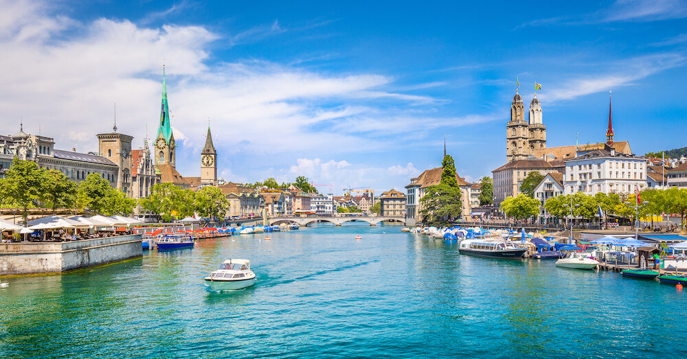 Panoramic view of historic Zurich city center with famous Fraumunster and Grossmunster Churches and river Limmat at Lake Zurich on a sunny day with clouds in summer Canton of Zurich Switzerland
