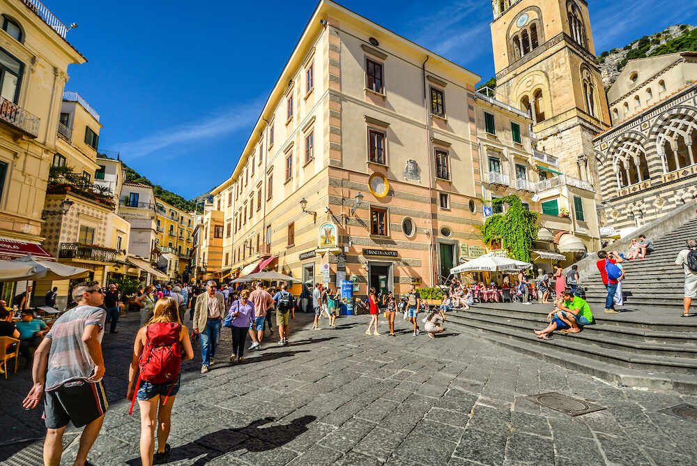 Amalfi, Italy - The center of the town of Amalfi on the Amalfi Coast of Italy with the stairs leading up to the famous Amalfi Cathedral as tourists shop and dine