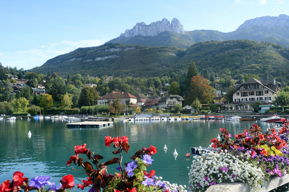 Annecy lake and Talloires village and marina with flowers on foreground Savoy