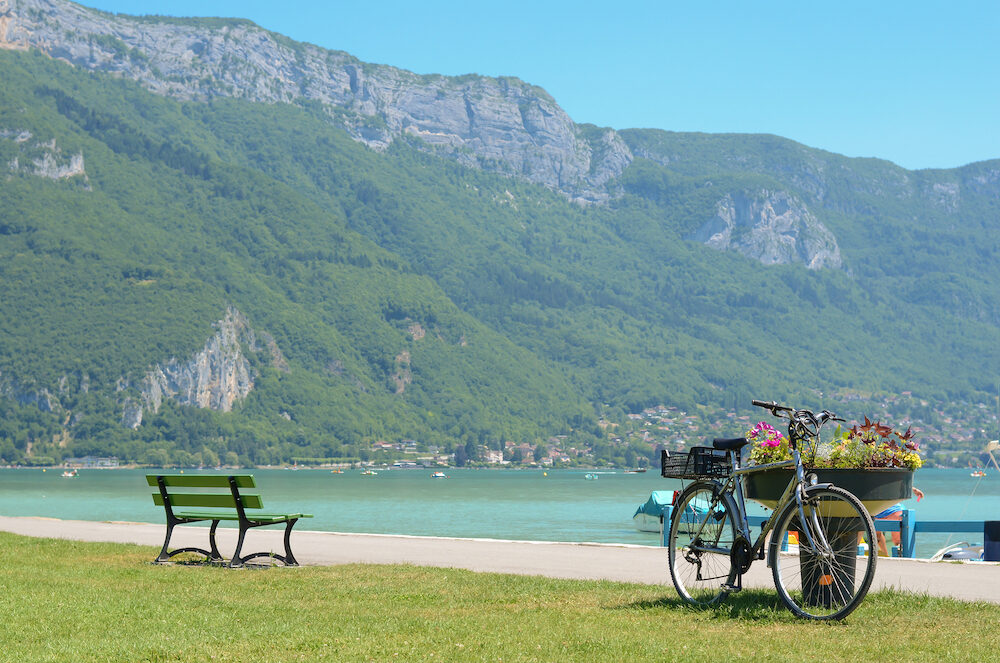 Bicycle parked in beach near mountains in Annecy