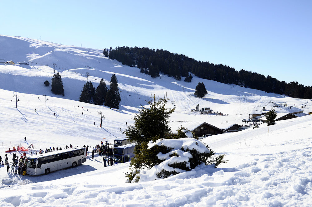 Ski station of Semnoz snow bus and skiers Savoy France