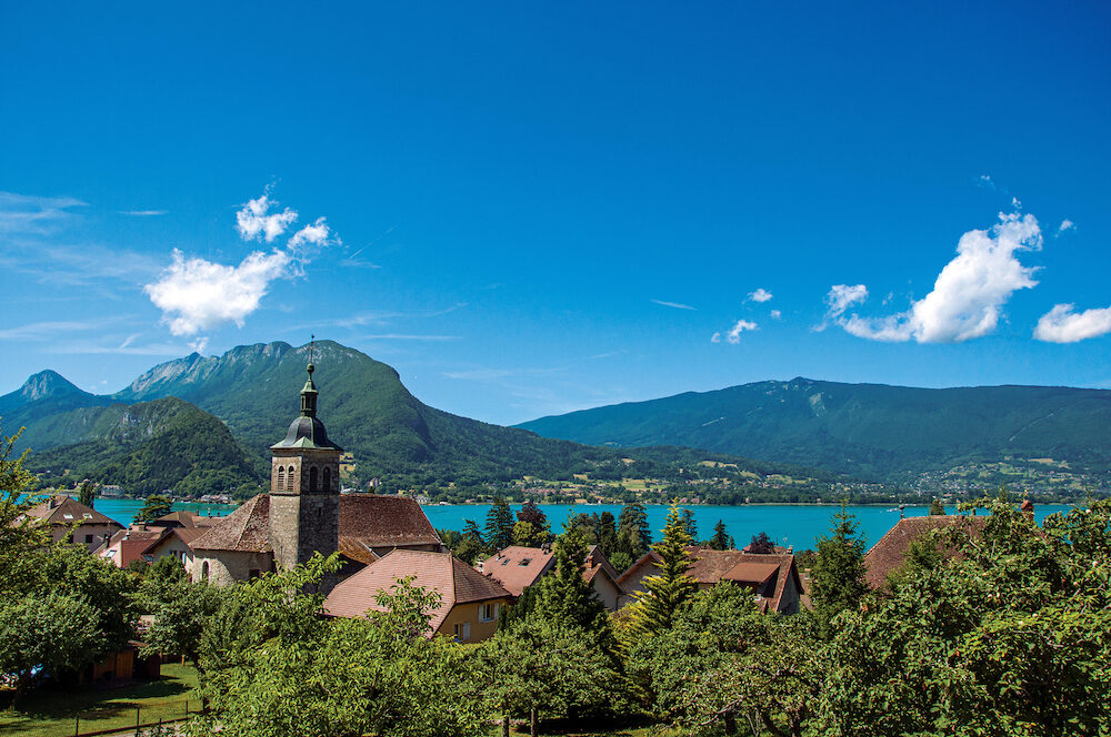 View of houses with belfry, in the village of Talloires, next to the Lake of Annecy. Mountains landscape on background, blue sky with clouds. France