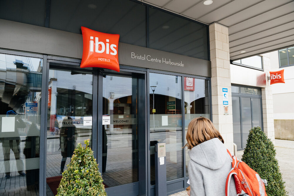BRISTOL UNITED KINGDOM - Woman entering the ibis hotel entrance welcome door with red signage and designed trees and red carpet - clean hotel with luxury entrance - Ibis Bristol Centre Harbourside