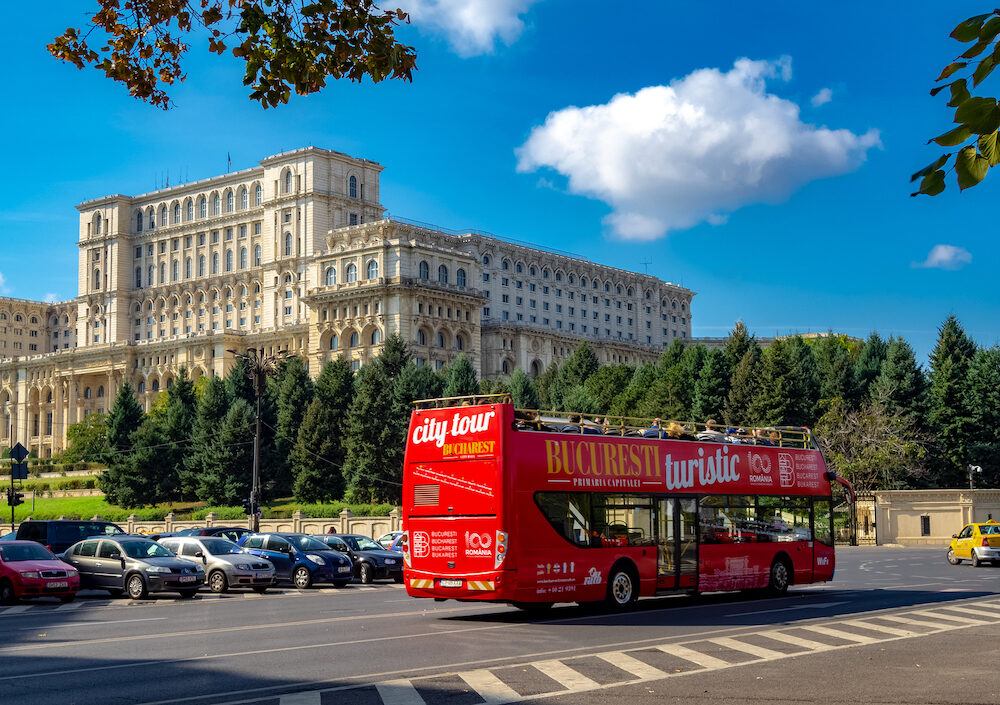 Bucharest, Romania - : Touristic city-tour bus in front of Parliament Palace architecture in a sunny day.