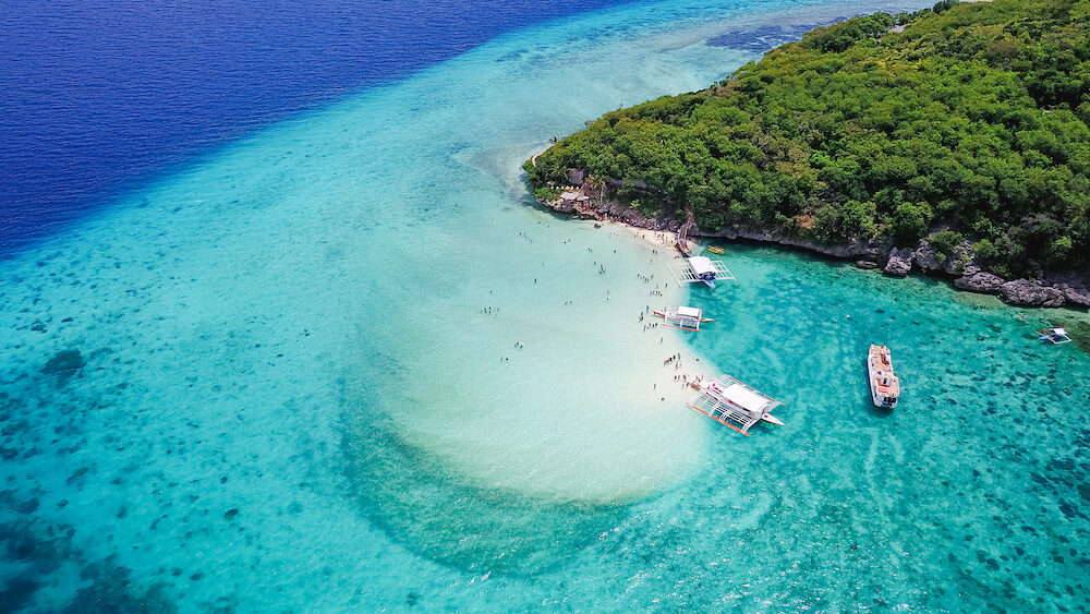 Aerial view of sandy beach with tourists swimming in beautiful clear sea water of the Sumilon island beach landing near Oslob Cebu Philippines. -