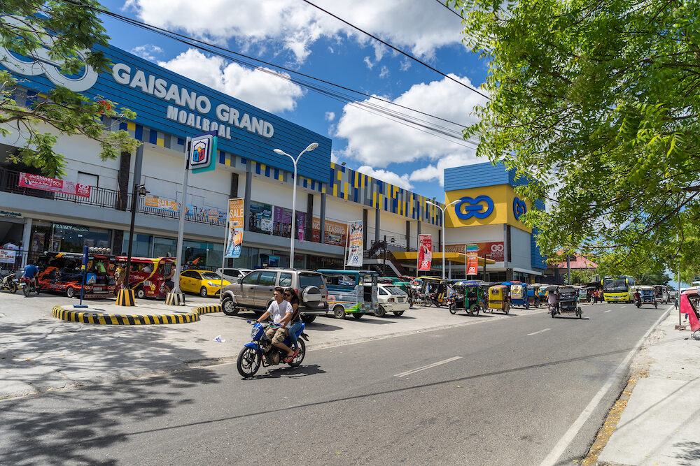 Moalboal. Cebu. Philippines - Mall Gaisano under blue sky near parking and road with motorcycle, bus and tricycle