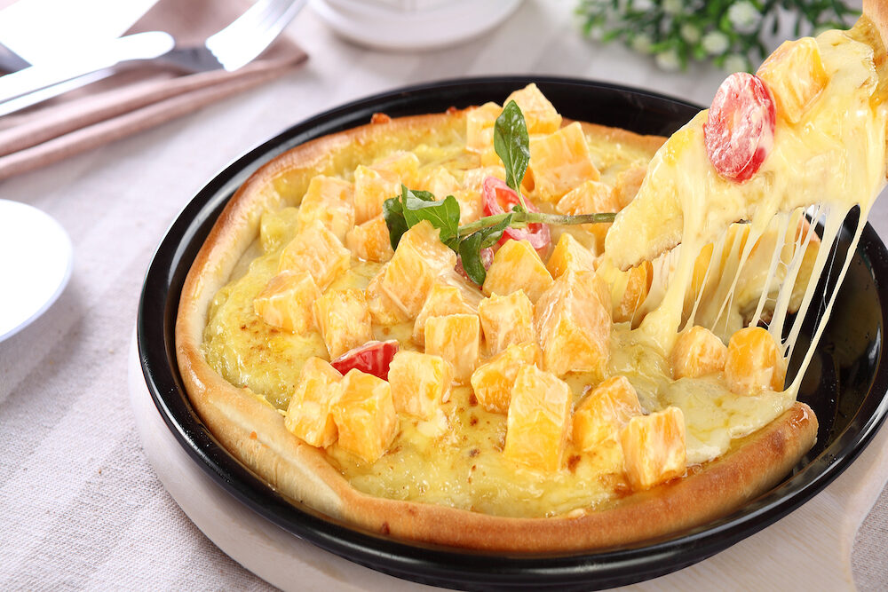 Mango cheese pizza in a black dish