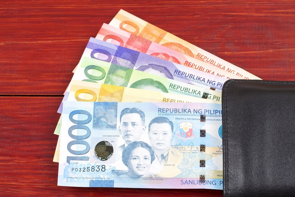 Philippine peso in the black wallet on a wooden background