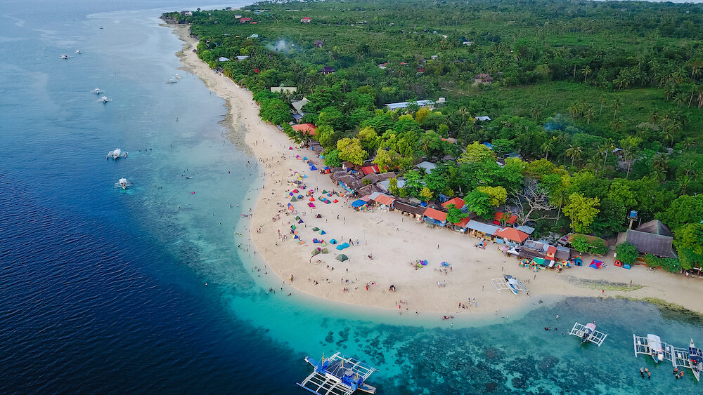 Aerial view of sandy beach with tourists swimming in beautiful clear sea water of the Sumilon island beach landing near Oslob Cebu Philippines.
